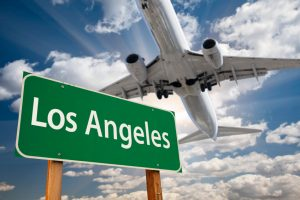 Image is a plane landing over a Los Angeles sign.