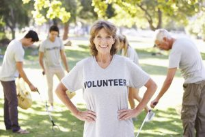 Volunteer Group Clearing Litter In Park Wearing Voulnteer T Shirt Smiling