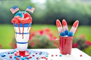 Image is red, white, and blue desserts and popsicles against an outdoor background.