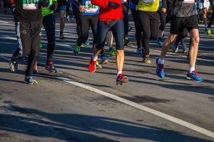 Image is of a group of marathon runners from the waist down.