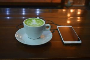 Image is of a green tea latte on a wooden table next to a cell phone.