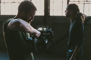 Image is of a man filming another man.