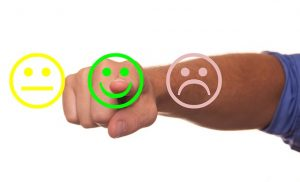Image is of neutral, happy, and sad smiley faces with a man's finger pointing at the smiley face.