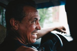 Image is of a smiling man behind the wheel of a car.