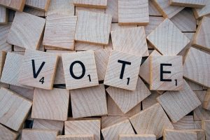 Image is of the word vote spelled out in scrabble tiles.