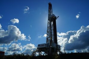 Image is of an oil well drilling platform against a blue sky.