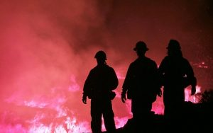 Image is of three firefighters against a wildfire background.