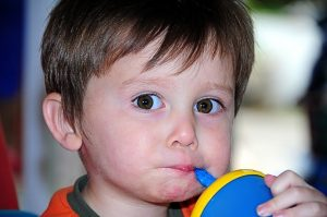 Image is a little boy drinking from a cup using a straw.