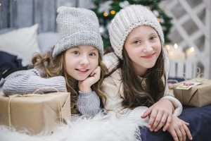 Image is of two girls in winter hats next to presents wrapped in brown paper with Christmas tree in background.