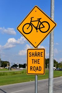 "Image is a yellow caution sign with a picture of a bike on it and a ""share the road"" sign underneath."