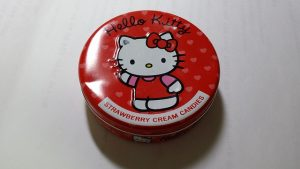 Image is a red tin of Hello Kitty strawberry cream candies.