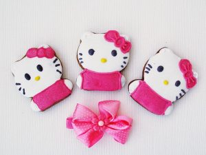 Image is of three Hello Kitty gingerbread cookies above a pink bow.