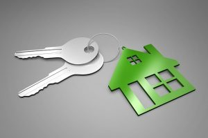 Image is a green keychain in the same of a house with two silver keys attached.