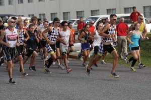 Image is a group of racers running on a city street.