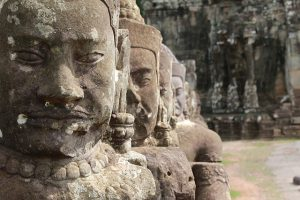 Image is a close up of statues in Angkor Wat in Cambodia.