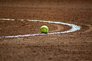 Image is a close up of a softball on a softball infield.