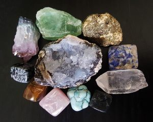 Image is a group of rough gemstones against a black background.