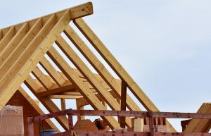 Image is roof trusses on a home under construction.