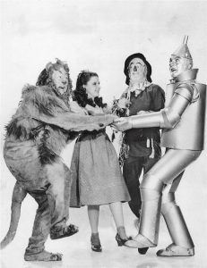 Image is a black and white photo of Dorothy, the Scarecrow, the Tin man, and the Cowardly Lion from the Wizard of Oz