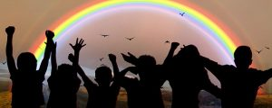 Image is a rainbow with children in front of it, cast in shadow.