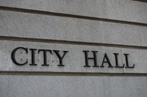 Image is a city hall sign on a brick building.