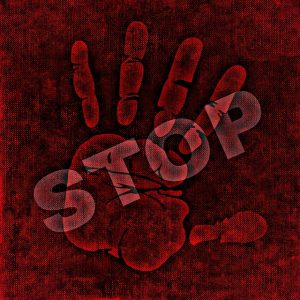 Image is a handprint with the word stop stamped over the top of it, with everything in shades of red.