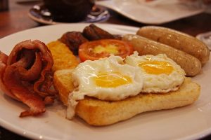 Image is a plate of bacon, eggs, toast, and sausage.