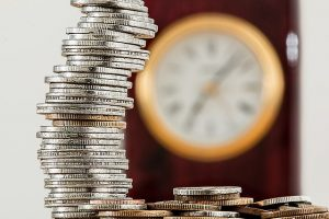 Image is a stack of coins with a clock in the background.