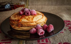 Image is a plate of pancakes with raspberries on top.