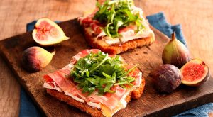 Image is two open faced sandwiches on a board with figs from Kustaa.