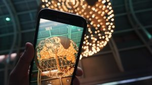 Image is a hand holding phone taking picture of a lighted globe.