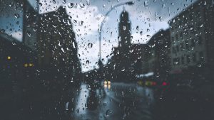 Image is a city skyline seen through a rainy window.