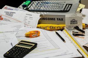 Image is a group of books, a calculator, and paperwork implying that someone is doing their taxes