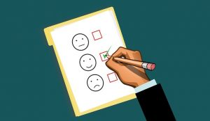 Image is an illustration of a survey with a hand checking the smiley face option rather than the neutral and sad faces.