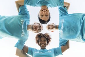 Image is four people locking arms in a circle and look down at a camera on the ground.
