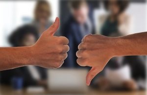 Image is two male hands, one giving the thumbs up sign and one giving the thumbs down sign.