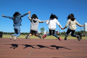 Image is four girls jumping in unison while holding hands with backs to the camera.