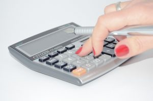 Image is a woman's hand holding a fountain pen while using a calculator.
