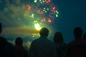 Image is a group of people watching a fireworks show.
