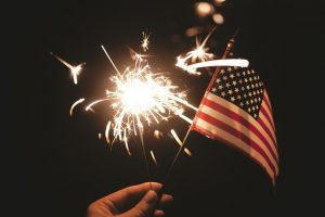 Image is a close up of a person's hand holding a sparkler and a small United States Flag.