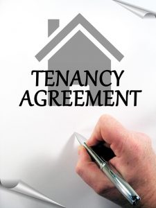 Image is a hand signing a tenancy agreement.