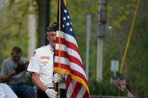 Image is a Veteran Holding an American Flag.