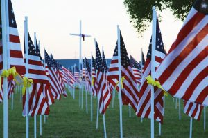 Image is a field of American Flags with yellow ribbons tied on each flag pole.