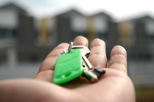 Image is a close up of a hand holding property keys with townhouses in the background.