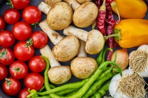 Image is a close up of a bunch of food, such as tomatoes, mushrooms, peppers, green beans, and garlic.