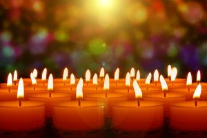 Image is a bunch of lit tea light candles with Christmas lights in the background.