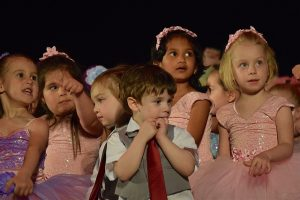 Image is a group of children dressed to perform.