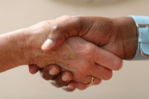 Image is a close up of two women shaking hands.