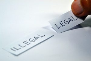 Image is a close up of someone putting a paper with the word legal next to a paper with the word illegal written on it.