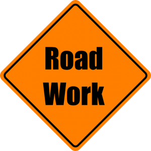 """Image is a yellow road sign that says """"road work."""""""